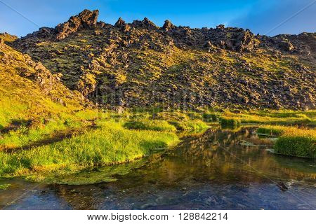 Lake with hot water on the source of thermal water. Sunrise Park Landmannalaugar. White nights in Iceland