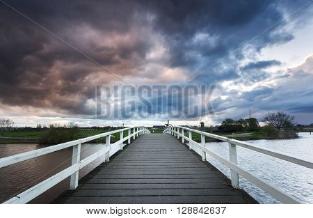 Wooden Bridge On The Background Of Dramatic Cloudy Sky