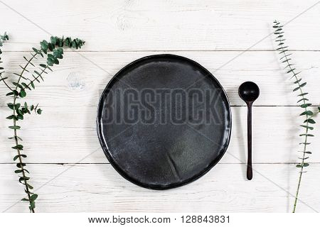 Top view empty black plate and cutlery on rustic wooden table. Ceramic black plate and spoon on white wooden background with free space. Flat lay of handmade black dish on white wooden table.