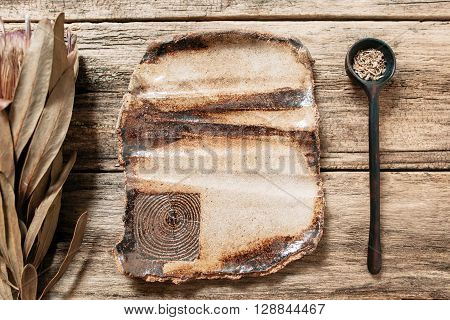Rustic handmade brown pottery empty big plate on wooden table. Creative brown ceramics with nature pattern. Empty clay dish and wooden spoon on old wooden background with freee space on plate