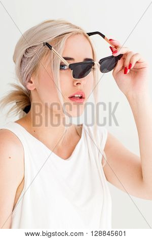 Holidays summer fashion eyes protection and skin care concept. Woman holding in hand black sunglasses, white background. Blonde girl wears sunglasses to protect herself from sun.