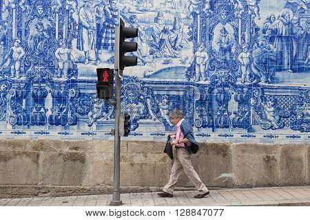 Man Walking Along A Typical Portuguese Decorated Wall