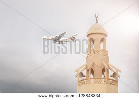 DUBAI, United Arab Emirates - DECEMBER 22, 2016: An Emirates aircraft is taking off from DXB airport near mosque