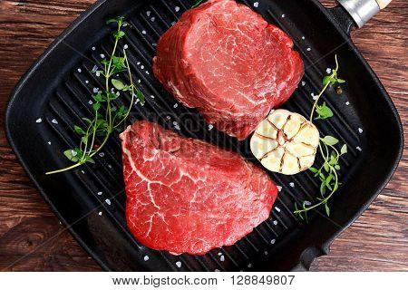 Fresh close up Raw Beef steak Mignon with thyme, garlic, salt on grilled pan