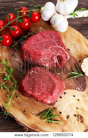 Fresh Raw Beef steak Mignon, with herbs on wooden board. ready to cook.