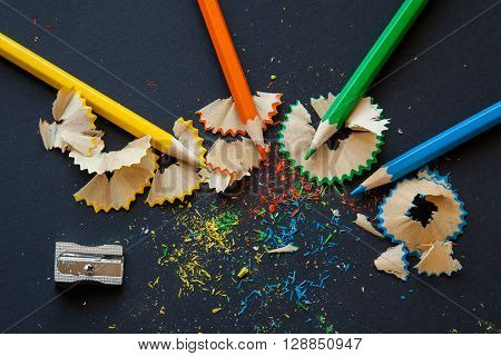 sharpener and wooden penciles with particles of sharpening on black