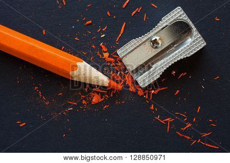 sharpener and orange wooden pencil with particles of sharpening on black