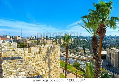 The old city walls surrounded by scenic palms and lush gardens making the ramparts walk more joyful Jerusalem Israel.