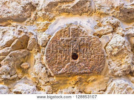 The medieval relief at the 8th station of Via Dolorosa on the wall next to the Greek Orthodox Monastery of Saint Charalampus Jerusalem Israel.