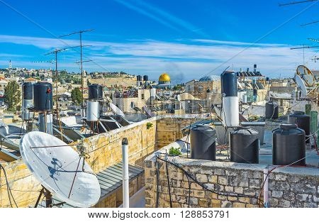 The golden cupola of the Dome of the Rock between the roofs water storage tanks and satellites of the residential houses in Jerusalem Israel.