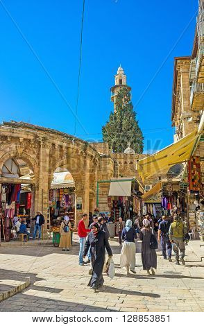 JERUSALEM ISRAEL - FEBRUARY 18 2016: The market street leading to the Church of the Holy Sepulchre and the Gate of the Aftimos Bazaar from the left on February 18 in Jerusalem.