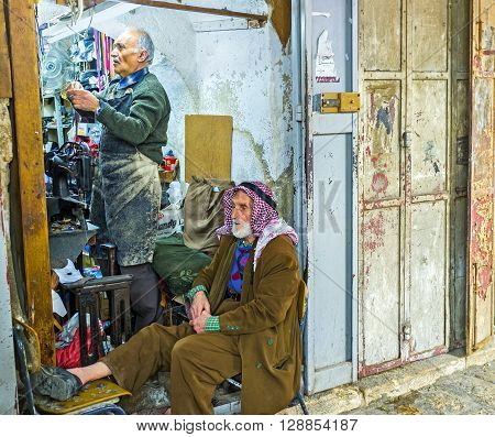 JERUSALEM ISRAEL - FEBRUARY 18 2016: The conversation of two old friends in shoemaker's workshop located in Muslim Quarter market on February 18 in Jerusalem.