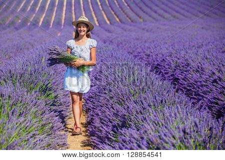 Beautiful young girl in hat with bouquet in the lavander fields in Valensole. Provence, France.