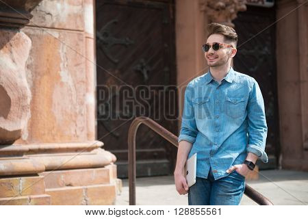 Enjoy your life.  Cheerful delighted handsome  smiling man holding tablet and leaning on the handrail while expressing gladness