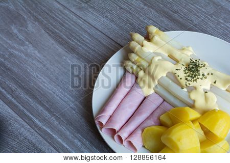 Plate With Asparagus Potatoes And Ham With Sauce Hollandaise