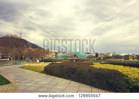 TBILISI GEORGIA - MARCH 11 2016: The Bridge of Peace is a bow-shaped pedestrian bridge over the Kura River in Tbilisi capital of Georgia.