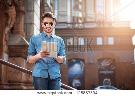 Lighten up my mood.  Positive content handsome man smiling and using tablet while leaning on the handrail