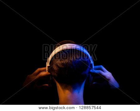 head of a teenager in headphones with hands