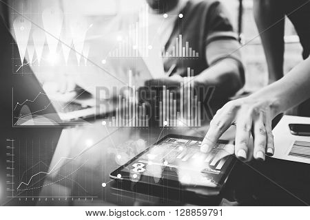 Business concept photo.Meeting of investment managers.Woman showing document.Man holding report, using laptop.Graphic icon, worldwide stock exchanges interfaces.Horizontal.Film effects.Black and White