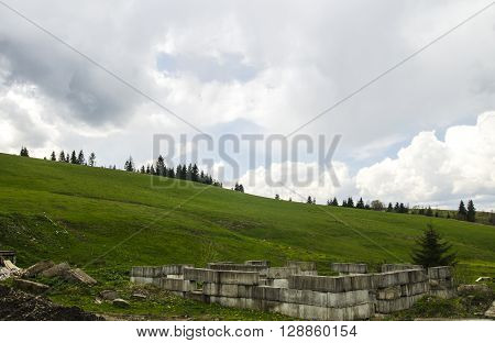 Mountain hills with green fields and meadows. Ruins of ancient castle in front of boundless fields