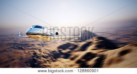 Photo of silver modern and luxury generic design private jet flying in blue sky at sunrise.Uninhabited desert mountains background.Business travel picture.Horizontal, motion blurred effect.
