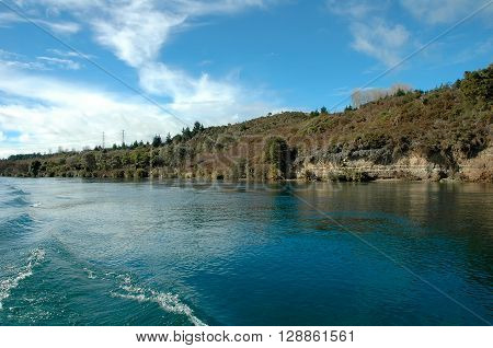 Blue waters of the river and the green river bank