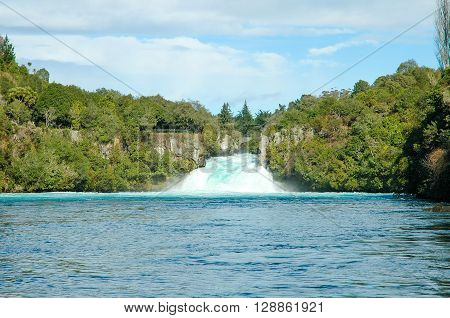 Vibrant blue waters in the foreground of Huka water falls in New Zealand against the forest and blue skies