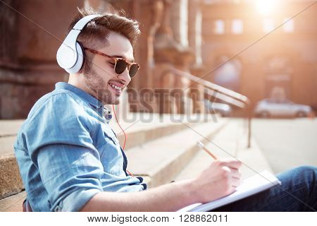Do what you like. Cheerful smiling handsome guy drawing and listening to music while resting on the footsteps