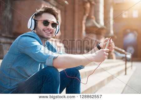 Find inspiration. Cheerful handsome smiling man sitting on the footsteps and listening to music while feeling glad