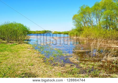 Rural spring landscape - backwater of Volkhov river and Yuriev monastery in the distance in nice spring weather. Spring colorful water rural landscape.