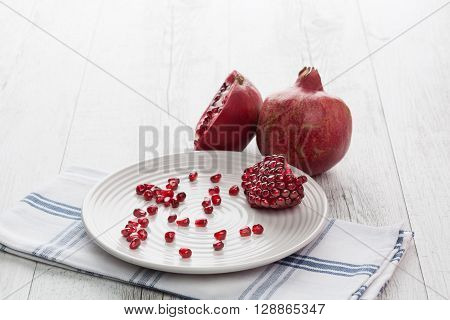 Pomegranate whole, half and seeds on white plate. Horizontal image with back lighting. Shallow depth of field.
