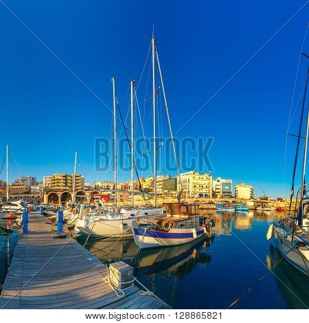 Old harbour of Heraklion with fishing boats and marina in the summer sunny morning, Crete, Greece.