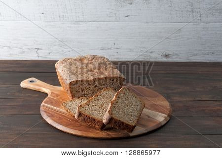 Homemade dark rye sourdough bread loaf and sliced on round chopping board. Horizontal image with copy space.