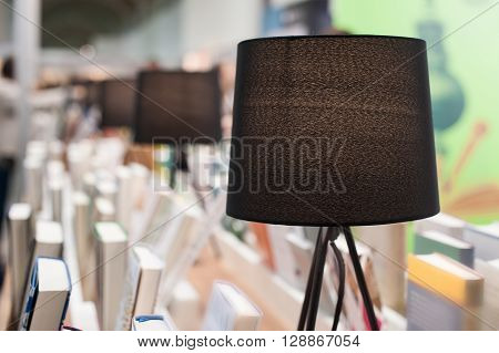 Electric brown table reading lamp and books in a library.
