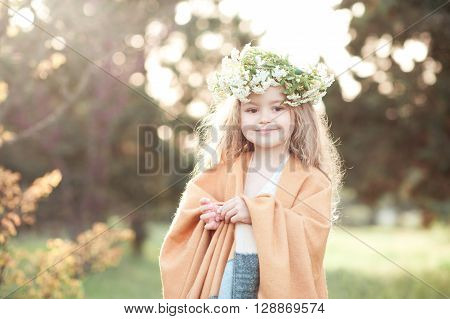 Smiling baby girl 3-4 year old wearing flower wreath outdoors. Looking at camera.
