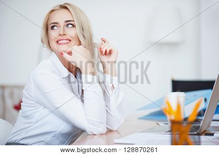 Self sufficient person.  Cheerful content charming woman smiling and sitting at the table while expressing gladness in the office