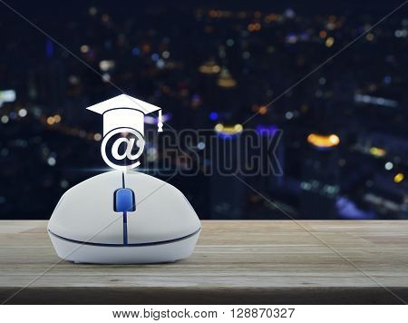 Wireless computer mouse with e-learning icon on wooden table in front of blurred light city tower Study online concept