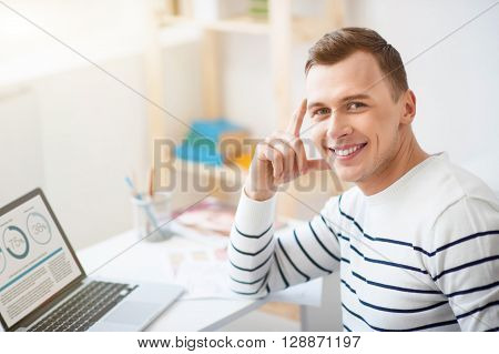 Gladness in mind. Cheerful positive smiling handsome man sitting at the table and working on the laptop while expressing joy