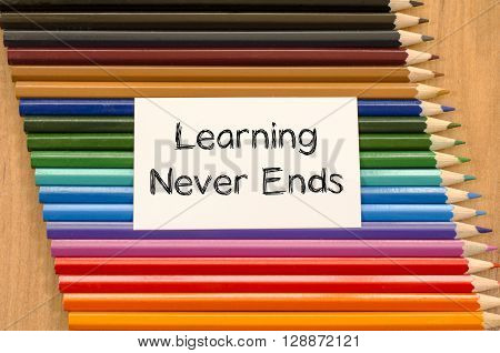 Learning never ends text concept and colored pencil on wooden background
