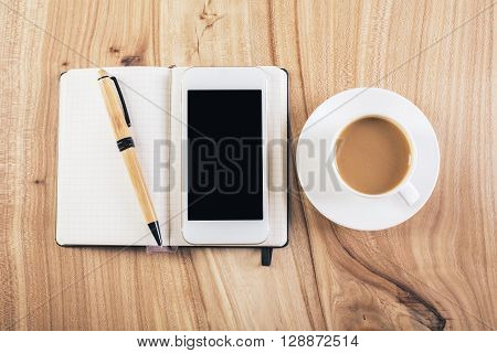 Topview of wooden desktop with blank smartphone on notepad and coffee cup. Mock up