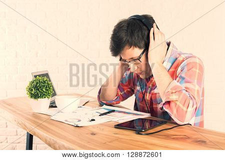 Caucasian male trying to concentrate over wooden desk with business report tablet small green plant and other items. Brick wall background