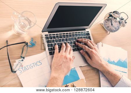 Sideview of male hands using blank black laptop on office desk with business report glass of water and alarm clock. Mock up