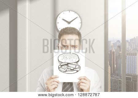 Frowny businessman can't wait for lunch break holding hamburger sketch in office interior with clock and city view. 3D Rendering