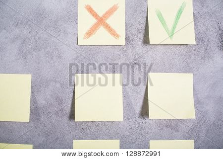 Closeup of paper stickers with cross and green tick glued onto grey concrete wall
