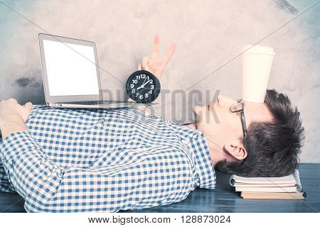 Sleepy caucasian businessman with blank white laptop and coffee cup on forehead lying on office desk and showing peace sign. Mock up