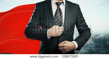 Businessman with red superhero cape on city background