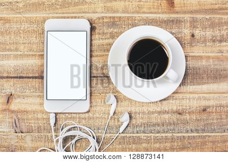 Topview of phone with headphones and coffee cup on antique wooden table. Mock up