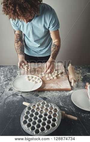 Tattooed Curly Chief Man Cooks Pelmeni Or Ravioli In Special Mold. Collecting Dropped Dumplings In H
