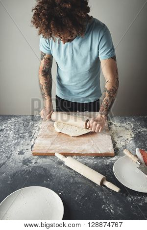 Tattooed Curly Chief Man Cooks Pelmeni Or Dumplings Or Ravioli In Special Mold. Flatten Dough On Mol