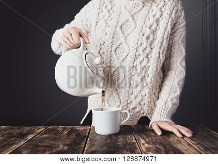 Woman In Cozy Warm White Thick Knitted Sweater Pours Hot Tea From Big Ceramic Teapot To Blank Cup On